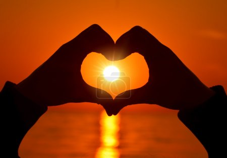 Photo for Heart shapewith hands  on sunset - Royalty Free Image