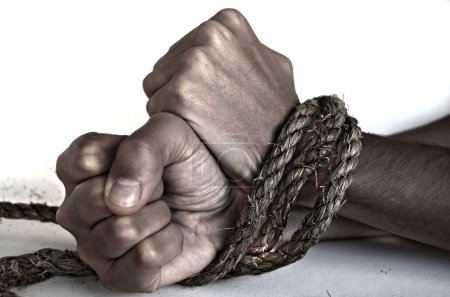 Hands of woman tied up with rope