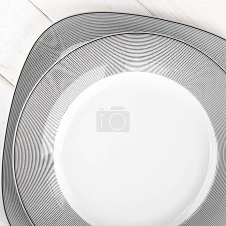 Photo pour Assiettes rondes blanches en porcelaine classique avec un motif gris sur une table en bois blanc - image libre de droit