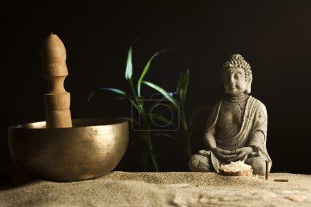 stone sitting buddha and Tibetan bowl