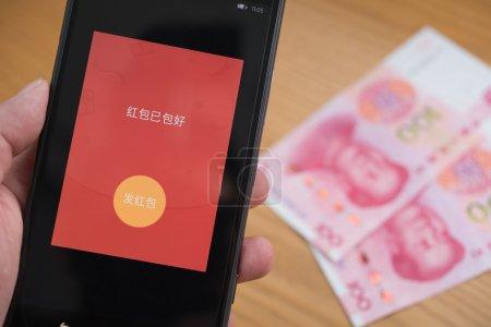Photo pour Zhongshan, Chine-Feb 21, 2016 : une poche rouge sur mobile est prête à être envoyé sur Wechat pour le nouvel an chinois avec Rmb sur fond. Le 8 février est le 1er jour de l'année du singe & envoyer recevoir des poches rouges en ligne est très populaire en Chine. - image libre de droit