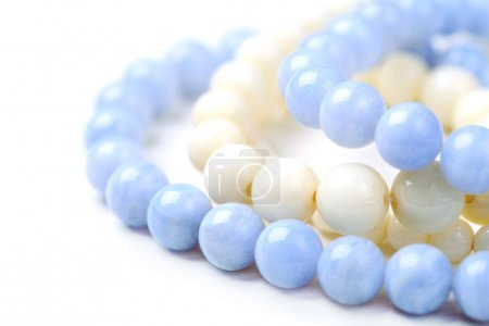 Bead necklace made from blue agate and white coral on a white table