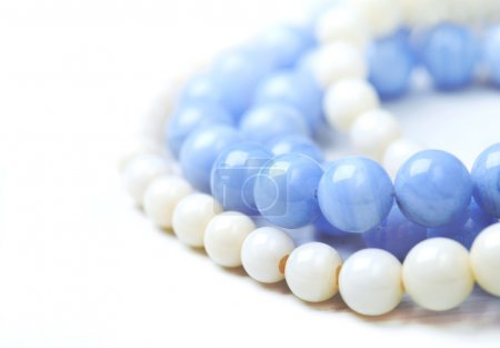 bead necklace made from blue agate and white coral on a white ta