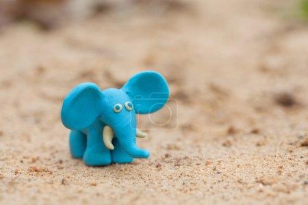 Plasticine world - little homemade blue elephant on a sand backg