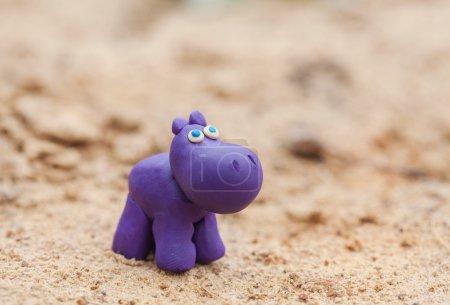 Photo pour Monde plasticine - petit hippopotame violet fait maison sur fond de sable, mise au point sélective et place pour le texte - image libre de droit