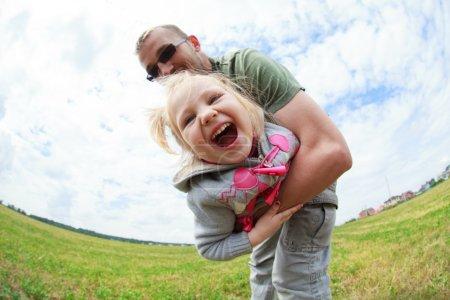 Photo pour Papa jouant avec sa petite fille, il la tourne autour de lui, mise au point sélective, l'effet de fisheye (perspective ) - image libre de droit