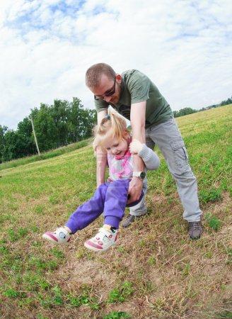 Photo pour Papa secoue sa petite fille dans ses bras comme sur une balançoire, foyer sélectif, l'effet du mouvement et fisheye - image libre de droit