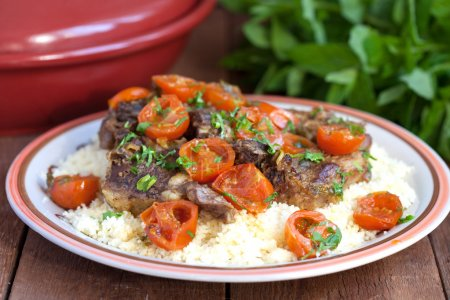 Moroccan tagine with lamb, tomatoes and couscous on a wooden tab