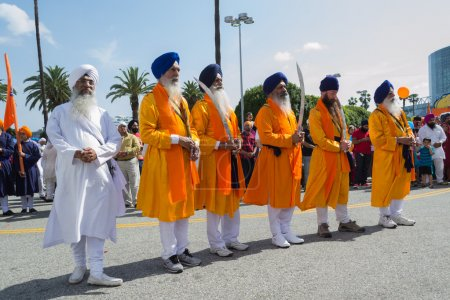 Devotee Sikhs with blue turbans holding swords