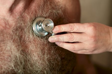 Phonendoscope - stethoscope on a hairy male chest. The doctor listens to heart
