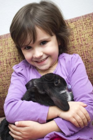 Preschool girl playing with rabbit