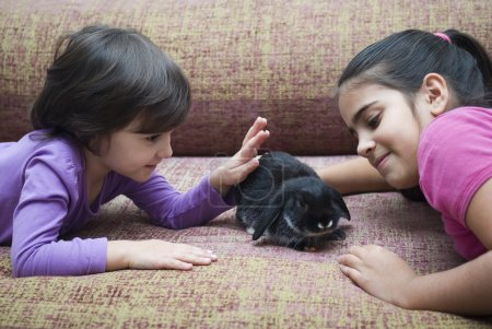 Girls playing with rabbit
