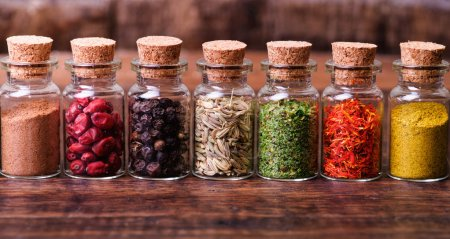 Spices in bottles on wooden background...