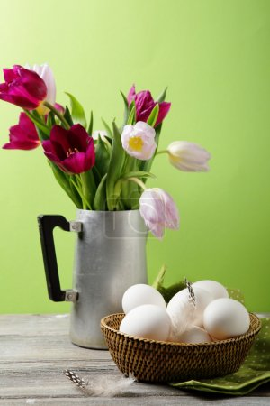 flowers in vase and eggs on basket