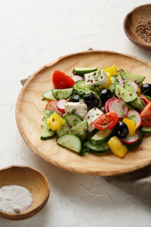 Fresh Greek salad on wood plate