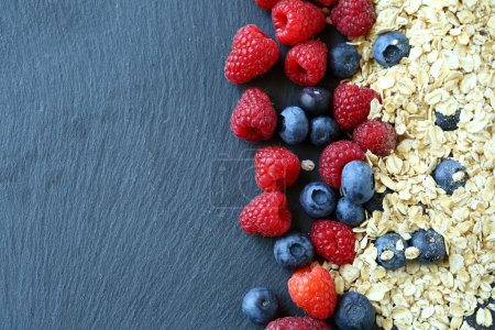 Photo for Healthy breakfast and berries on slate background, close-up - Royalty Free Image