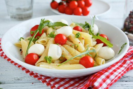 Pasta with vegetables and slices of mozzarella cheese in a plate