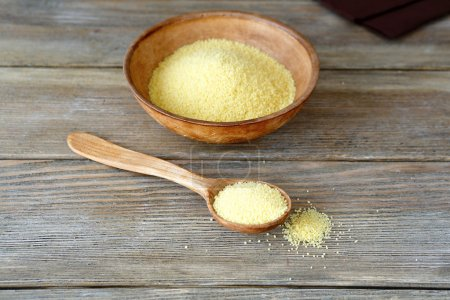 Couscous in a clay bowl and wooden spoon