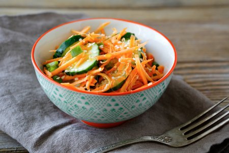 Vegetarian salad with carrots and cucumbers in a bowl