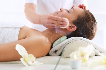 Cleansing facial skin, a woman in beauty salon