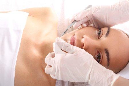 Photo pour Femme blanche pendant la chirurgie à l'aide d'un scalpel - image libre de droit