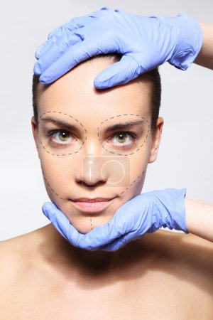 I want to be beautiful! Head of a Woman in the hands of a plastic surgeon