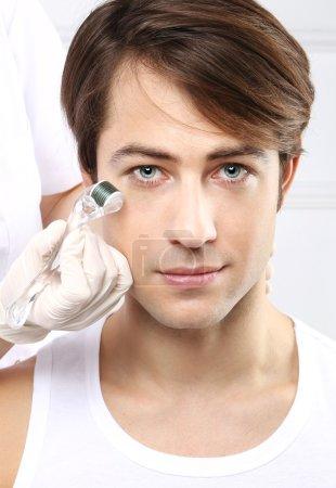 Photo pour Portrait d'un jeune homme soigné pendant le traitement dans le salon de beauté - image libre de droit