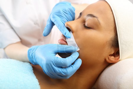 Depilation with hot wax mustache in the beauty salon