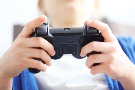 Photo for Child holding a remote control in his hand video games. - Royalty Free Image