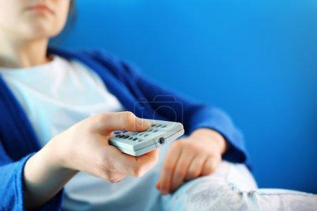 Photo pour Un adolescent change de chaîne sur la télévision en utilisant la télécommande - image libre de droit