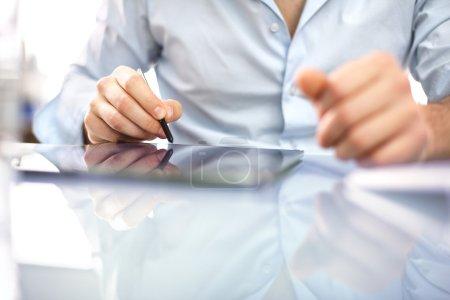 Photo pour Beau homme assis à un bureau - image libre de droit