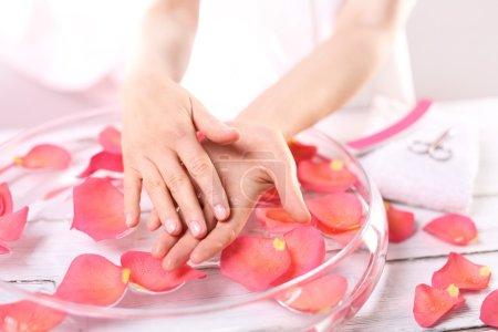 Photo pour Traitement de soin des mains et des mains de femme de clous au-dessus du bol avec des pétales de rose - image libre de droit