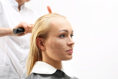Clipping, combing woman at the hairdresser