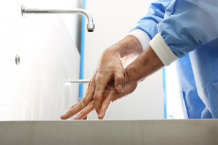 Photo for The doctor washes his hands, disinfect their hands before surgery - Royalty Free Image