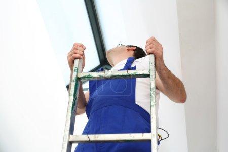 A man on a ladder.