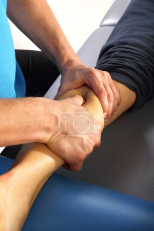 A physiotherapist massaged patient's leg.
