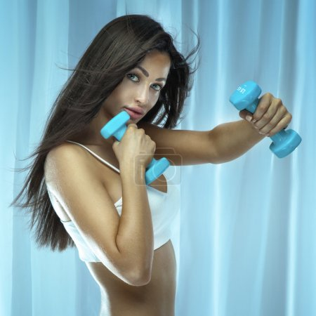 Athletic brunette woman doing workout.