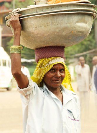 indian woman carrying a heavy basket on her head