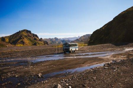 Photo pour Bus touristique à travers la rivière - image libre de droit