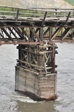 Wooden bridge in Yakutia across the mountain river.