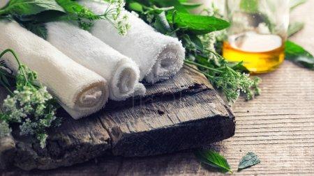Photo pour Spa ou paramètre de bien-être. Serviettes de bain, huile arôme dans la bouteille sur fond en bois âgé - image libre de droit