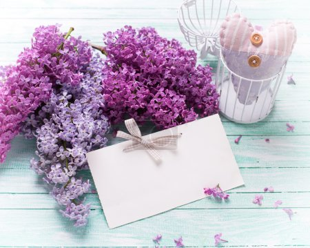 Photo for Background  with fresh lilac flowers,  textile decorative heart  and empty tag on turquoise painted wooden planks. - Royalty Free Image