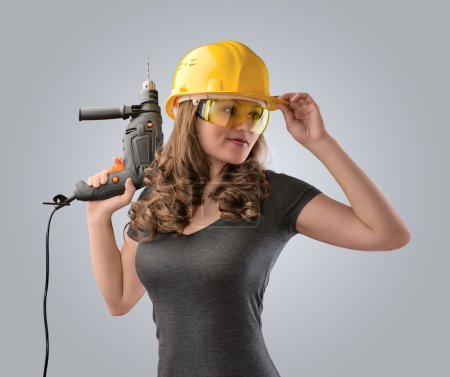 Worker girl in a helmet with a drill on a gray bac...