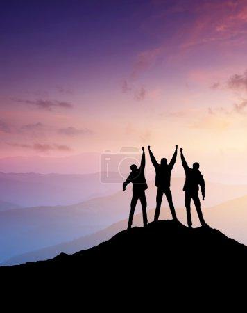 Silhouettes of team on mountain peak