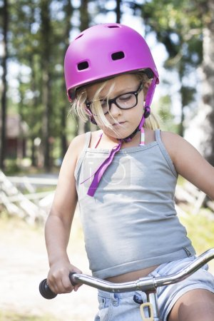 Girl with pink helmet, black glasses and bicycle