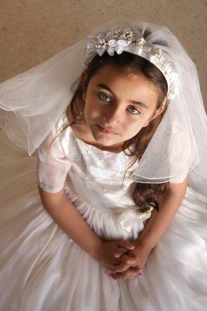 Photo pour Enfant faisant sa première communion vêtue d'une robe blanche et d'un voile, regardant la caméra, priant - image libre de droit