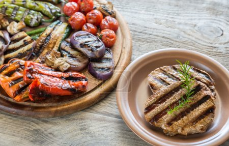 Grilled vegetables with beef steaks on the wooden board