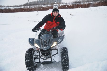 The young man at the time of extreme quad biking in the winter