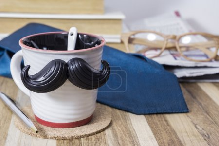 Cup with mustache on wooden table for fathers day concept