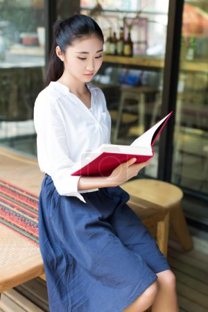 reading her favorite book in cafe